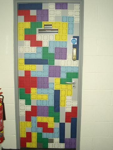 A door covered in pieces of paper, shaped and looking like Netris blocks.